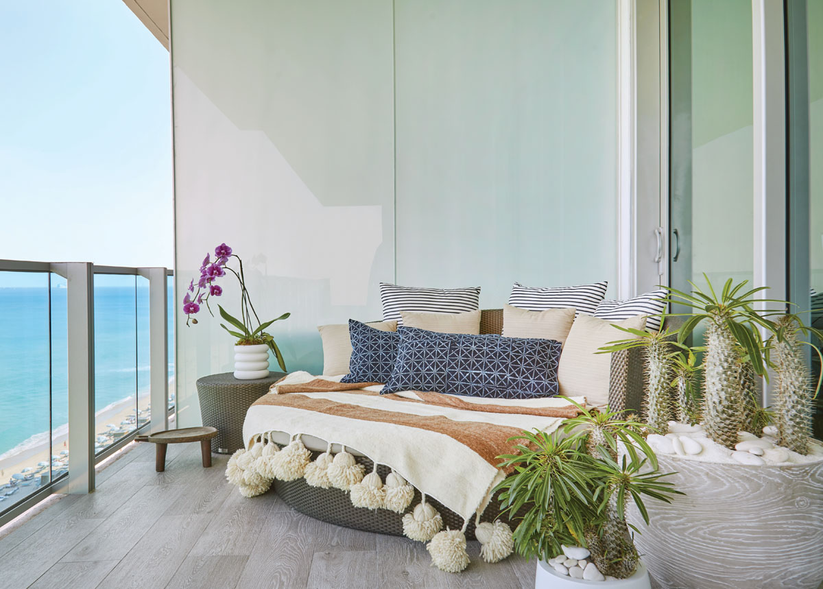 A round JANUS et Cie daybed accessorized with vintage batik lumbar pillows and a handwoven Peruvian blanket offers an inviting nook for sunrise contemplation.