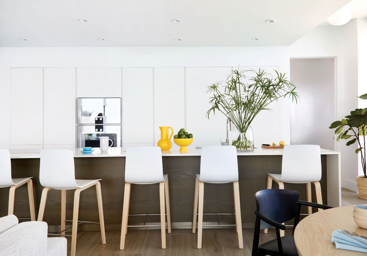 Weitzman retained the original kitchen design with white lacquer cabinets and an island paneled in gray-brown wood. She lined up simple Danish bar chairs from Suite NY to extend the contrast between the bright whites and wood elements.