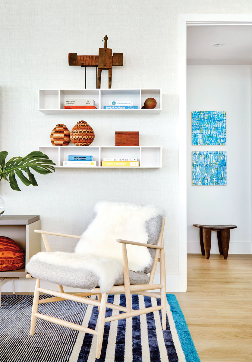 Hanging shelves house the designer's favorite art books and handicrafts sourced from local dealers. Two blue paintings by Weitzman herself elicit the flat graphic quality of textiles and hang above an African stool from the Watchful Eye African Art Gallery.