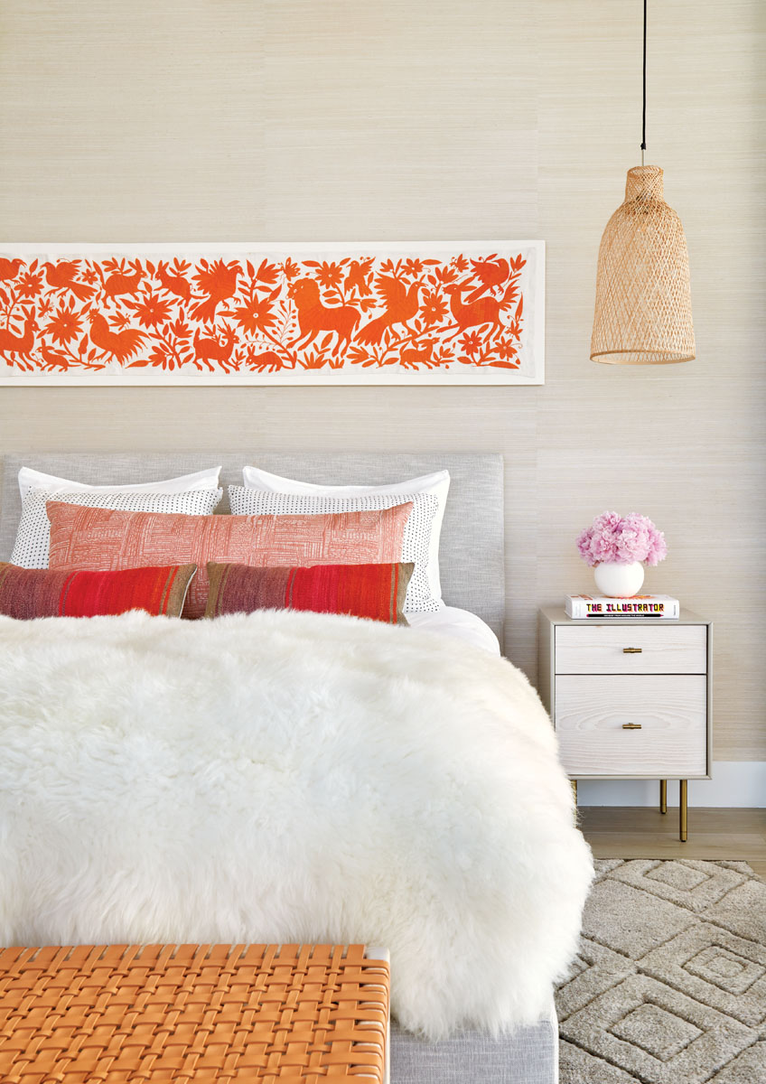 Inspired by her daughter, Weitzman designed the guest room in neutral hues and bright oranges, incorporating St. Frank and Rebecca Atwood pillows and a Mexican Otomi embroidery that she mounted on linen. Subtle textural juxtapositions are generated by a woven leather and wood bench from Made Goods and a bamboo pendant from Global Lighting.