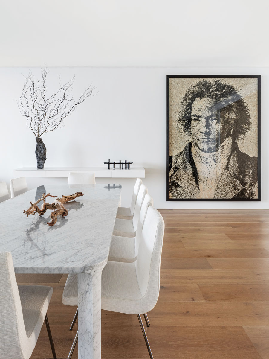 The dining area flows toward the living space, pared down to the essentials and the watchful gaze of Beethoven. But little things take on importance when showcased against museum white: a ceramic vase by Gilles Casier and a delicate pedestal from Jaime Hayon reside tranquilly on an unadorned shelf.