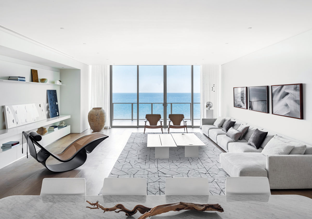 The living space is emphasized by the linear positioning of the sofa, the owner's own stone cocktail tables by Jacqueline Terpins, and the bank of shelving—all directing the eye toward the sea. A geometric mélange of channeled lines brings activity to the floor in Kelly Wearstler's silk and wool rug.