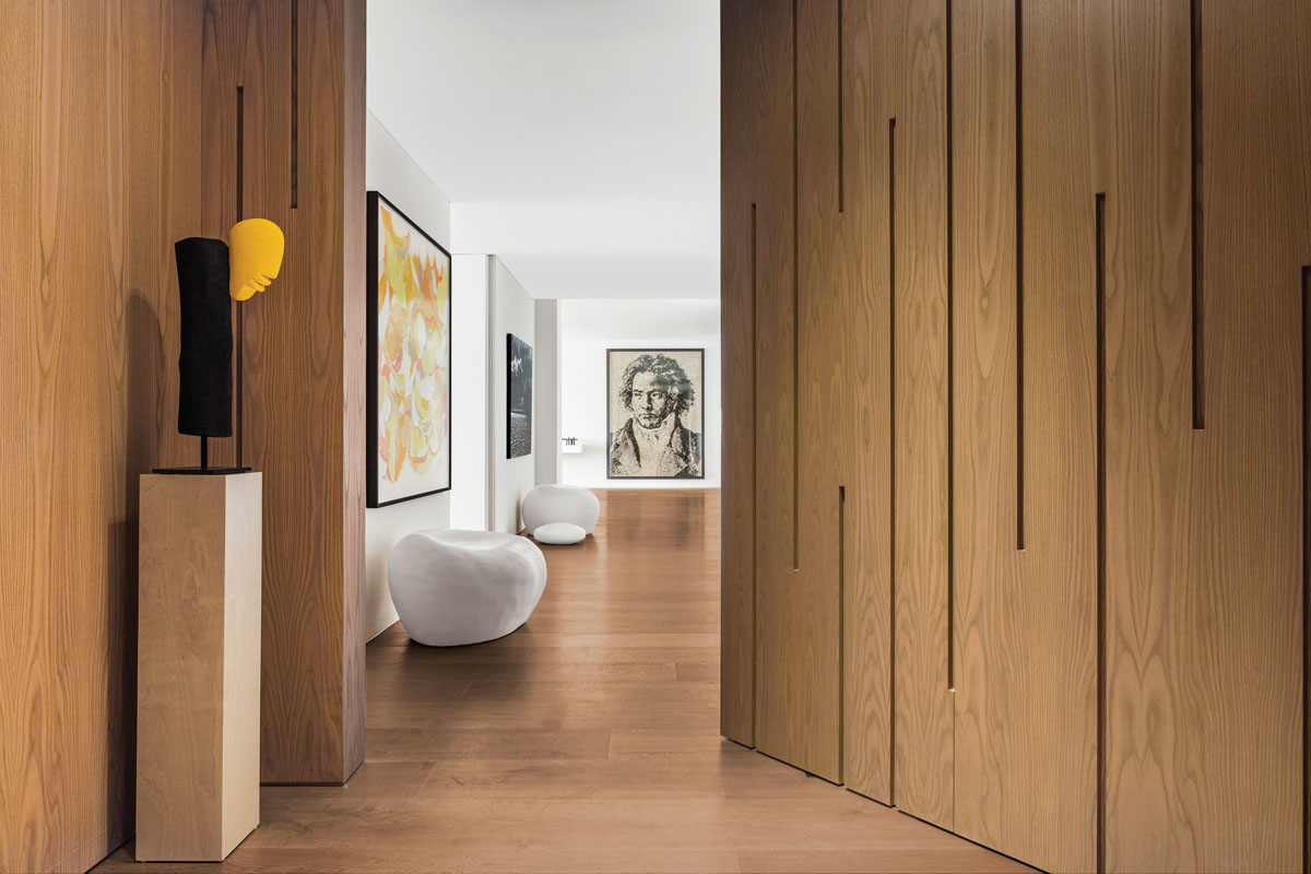 Hallways are opportunities. From the elevator entry into the living area, between which designer Jaegger installed a wall-size, pivoting oak door, guests find an invitation into a world of art. Johannes Beccer's pedestal-perched bust bids initial welcome. Inside, two round, white stone sculptures from Henry Moore stand guard.