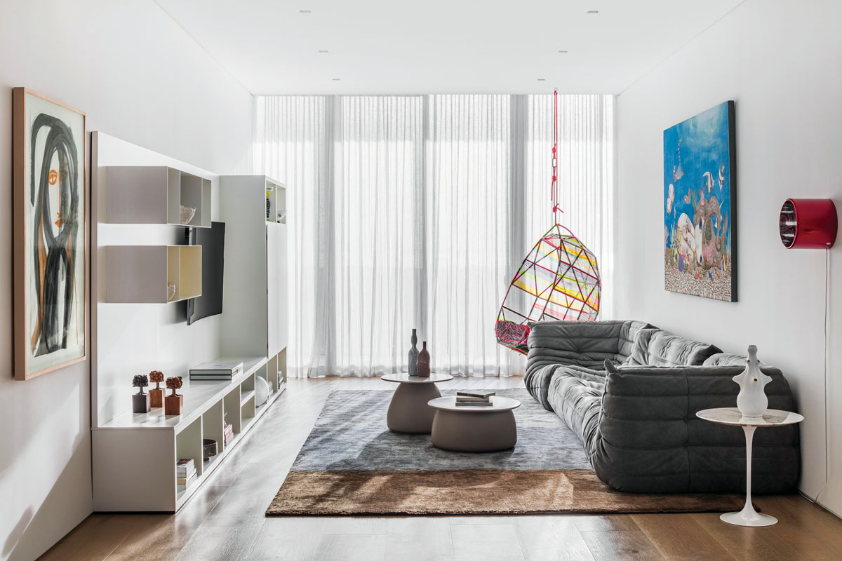 """The media room's informality is instantly apparent in the """"body-friendly"""" sofa. But shape and form are important, as seen in small sculptures, shelf design, ova-form tables, and Minotti's silk geometric rug. Wall art in blue from Nina Pandolfo and Heloisa Maia's portrait resonate with the brilliant hanging chair nearby."""