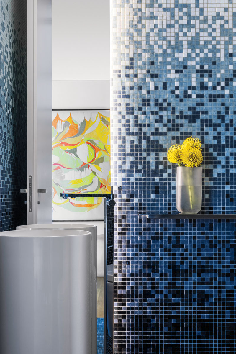 """A powder room captures in miniature the aesthetic """"glitz"""" of glass tile that is repeated in each of the other baths. For an """"ombre"""" feel, Jaegger designed the Bisazza tiles to be installed from dark to light. A slim pedestal sink and swan-like stainless faucet are reflected in a narrow mirror."""