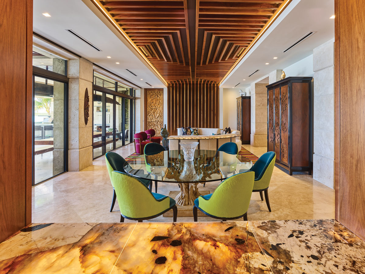 The homeowners brought some of their existing furniture with them to Miami, including a glass dining room table with sculptural base and surrounding green and turquoise chairs. Beatrice Pila-Gonzalez created a white circular couch to encourage conversation. De Leon crafted custom millwork that spans the ceiling and flows down the wall at the opposite side of the room.