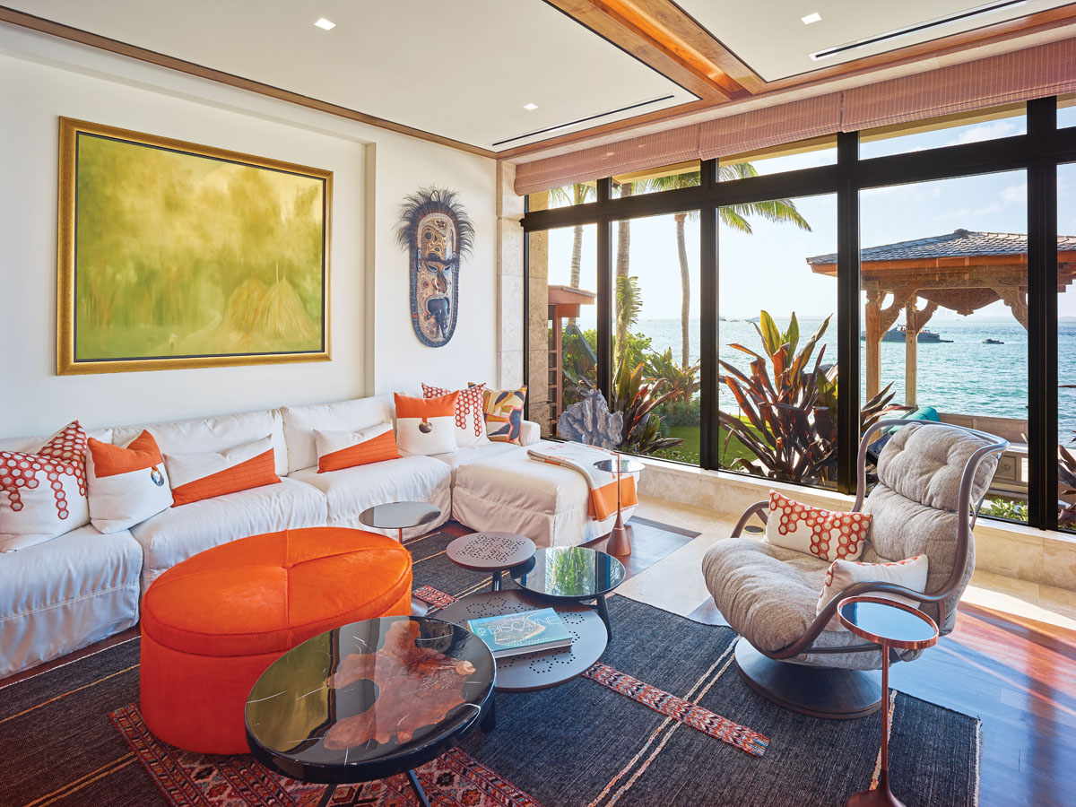"""Pila-Gonzalez created a user-friendly family room that is """"relaxed and very family-friendly."""" White slipcovers can be removed from the sofa and washed, while white leather chairs provide durable seating . Pila-Gonzalez then infused the space with Brazilian pieces (""""It works well with Balinese style because it's warm, but modern,"""" she says), tropical woods, and orange hues that were pulled from the nearby kitchen."""