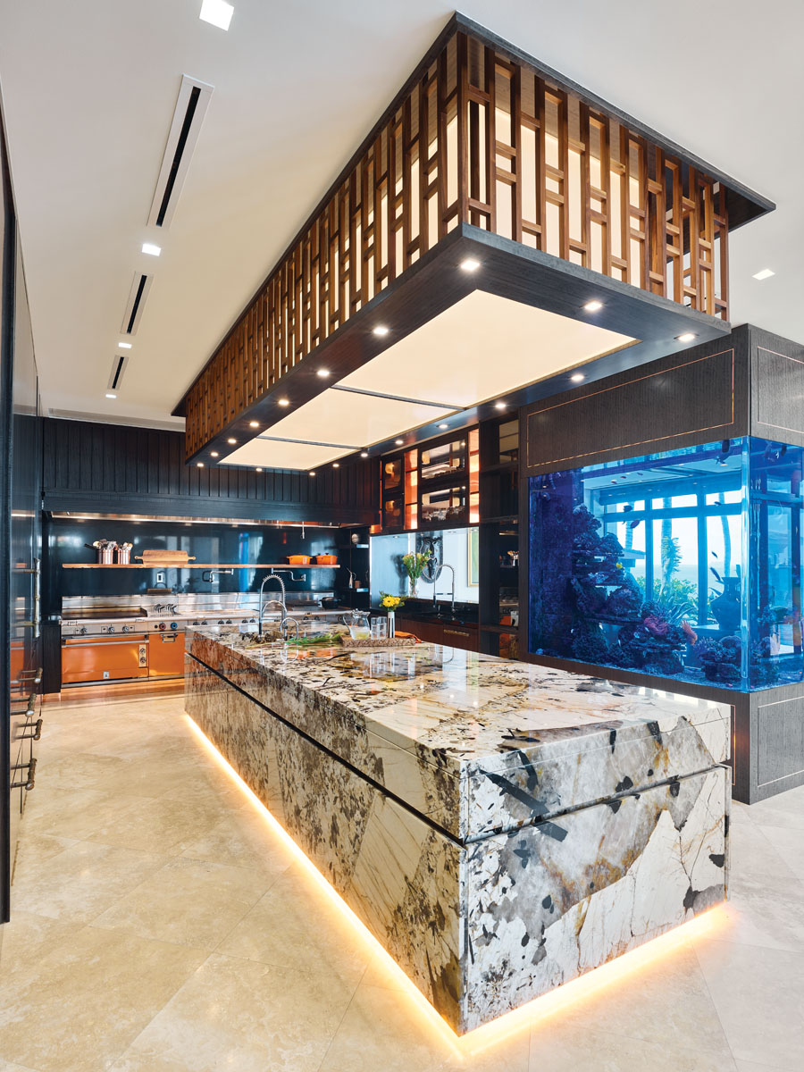 """De Leon constructed a model of the all-marble kitchen island to make sure the slabs fit together correctly before she assembled the larger piece. """"They had to bleed and blend together on all sides,"""" she says. Dark blue hues provide an elegant contrast to the marble centerpiece and the orange range, while a custom aquarium honors the surrounding seascape."""