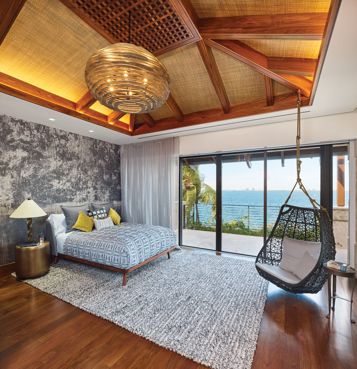 The couple's son has a peaceful retreat full of neutral hues, along with a sturdy swing and an expansive view of the water.