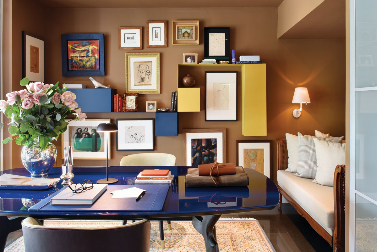 The wife's office is lined in sumptuous synthetic suede that complements the antique Persian rug. For contrast there is a modern Baxter chair and desk with a deep blue, high-gloss lacquered top. Modular blue and yellow box-like pieces from Roche Bobois offer clever hidden shelving.