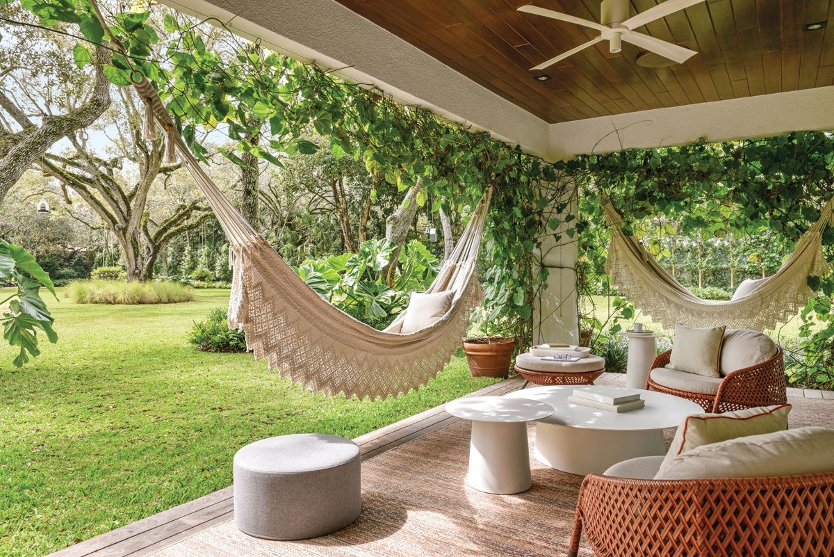 Two traditional hand-woven hammocks from Nicaragua beckon from the wood deck that was added to the breakfast terrace. The designer worked closely with the artisan who customized the weave to make the side skirts longer to pull it up as a cover and longer in length to fit the space.