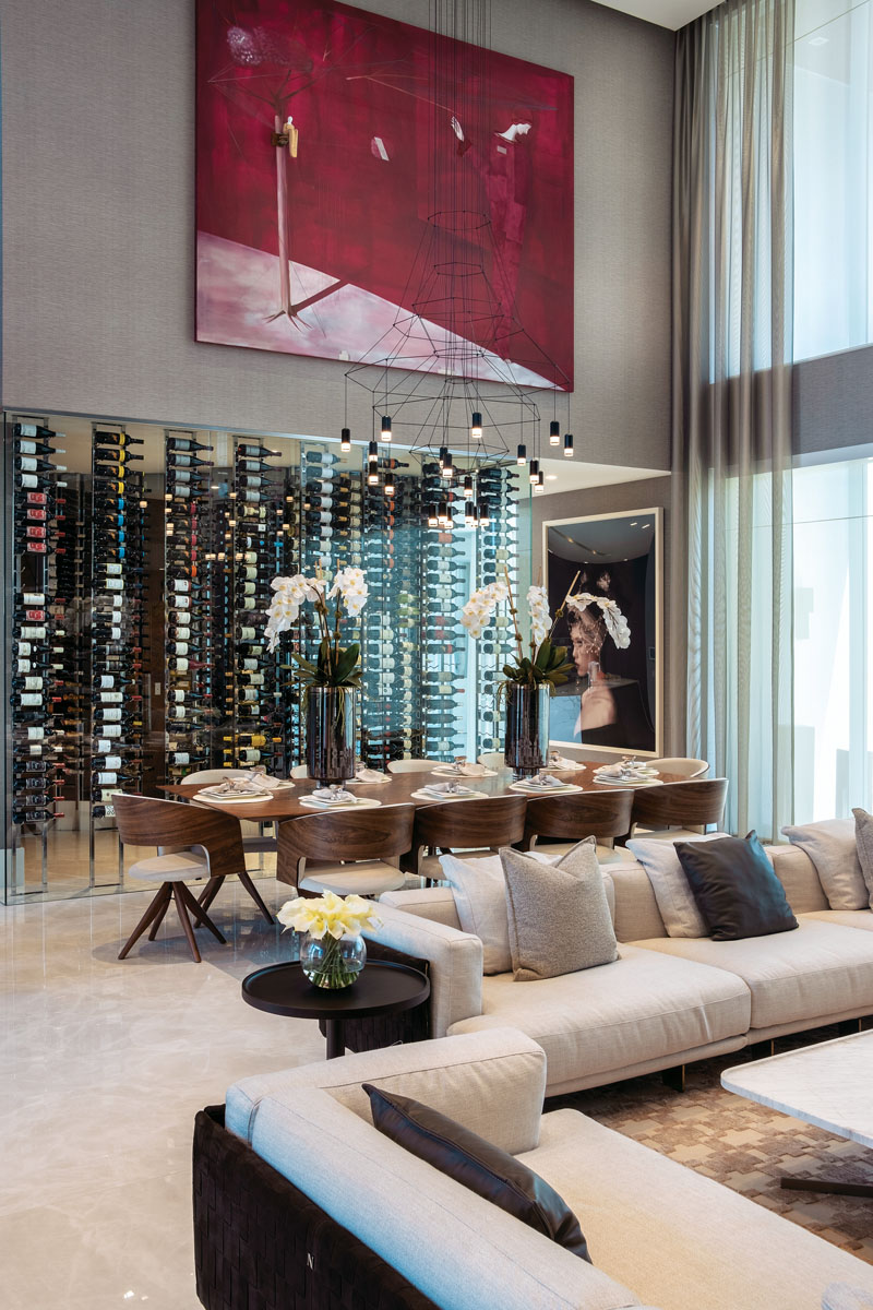 The great room is the center of activity and a nexus for entertainment. The wine cellar is a vertical divider, flanked by a walnut table and swiveling chairs by Roberta Schilling.