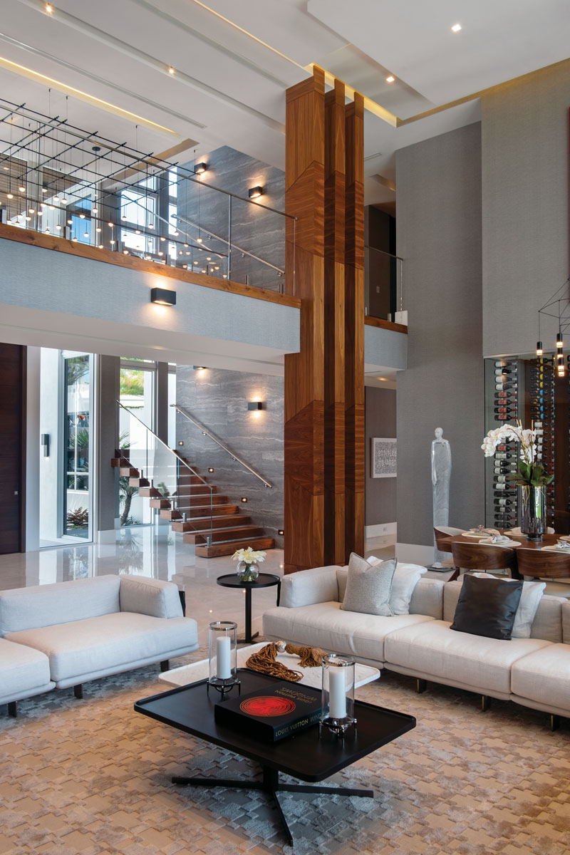 """Interior designer Michael Gray chose Natuzzi's cream-colored textured boucle for the sofa seating and woven nubuck suede along the back. Overhead, he positioned two 8-foot square monolithic chandeliers. Gray says its small lights reach in all directions, """"filling the space with twinkling lights that at night look as if the stars have entered the room."""""""