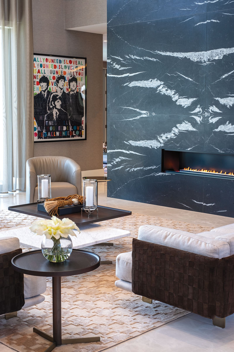 A custom-designed textured rug from Artistic Looms and the unobtrusive lines of a circular side and cocktail table allow the oversized stone fireplace to garner attention.