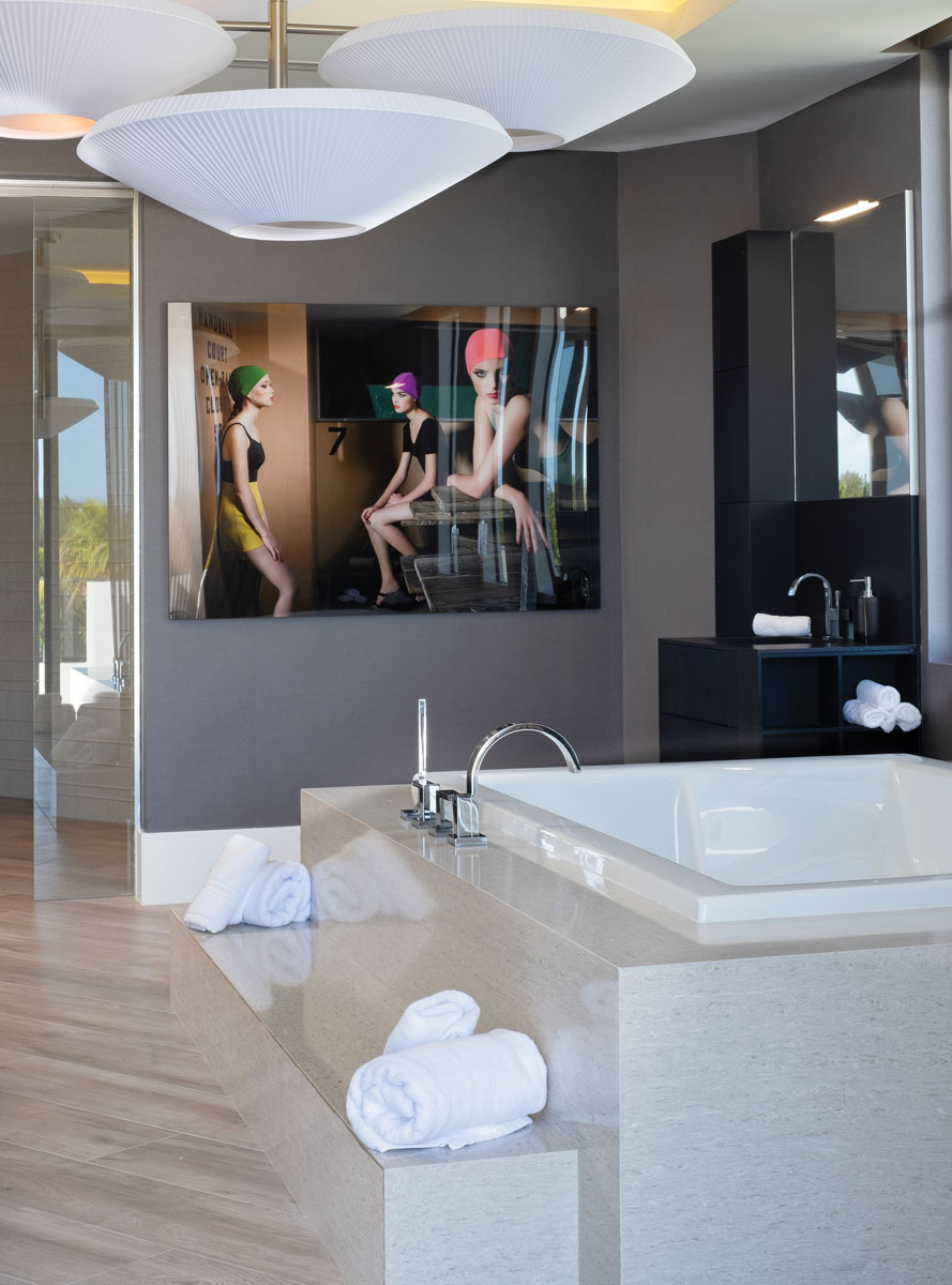 """The home's third-floor wellness center features an elegant marble bath with a free-standing central tub. Following a central theme of Zen serenity, Gray chose a ceiling light with Asian flair, brought to life with El Gee's softly lit """"inverted parasol"""" fixture."""