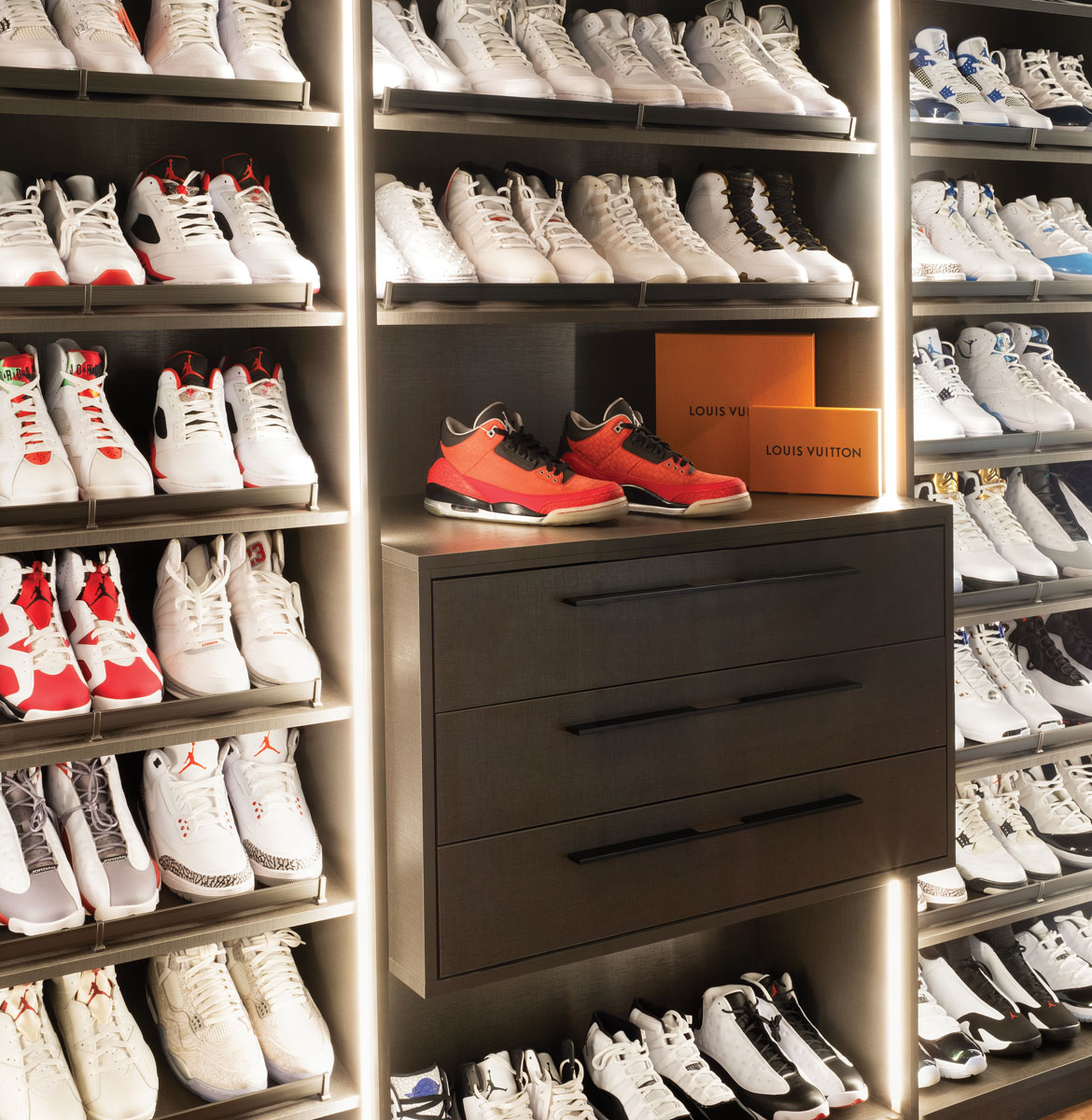 From the glass-encased pairs in the office to this custom closet, sneakerheads can rejoice in the care taken to display the homeowner's impressive collection of athletic shoes.