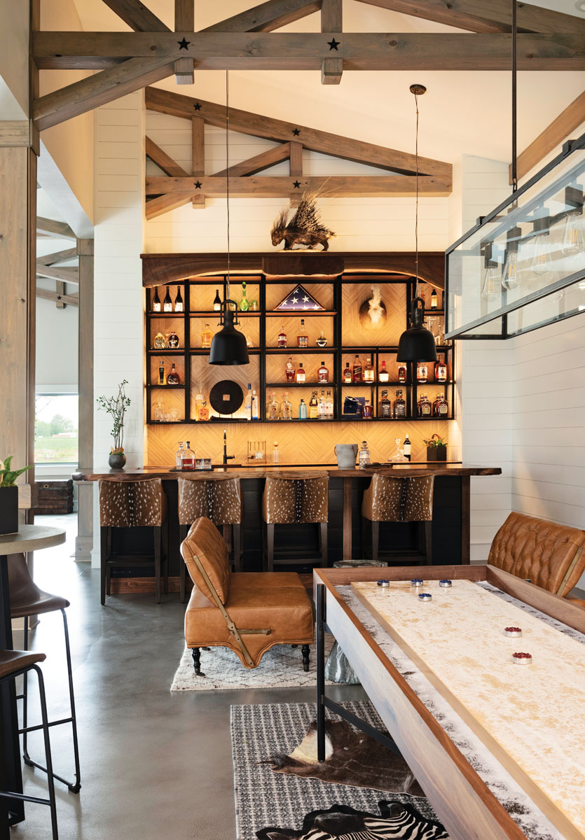 The Jimenez family wanted their bar and gaming area to feel warm and inviting. Animal hides, a live edge bar top, black marble on the back bar, a porcupine mount, and a custom shuffleboard table combine to make the space welcoming yet whimsical.