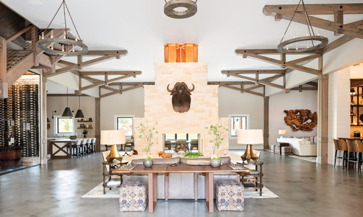 Visitors enter the main barn through a rustic steel door into the formal living room, with its open fireplace, water buffalo mount, and leather sofa. Poured concrete flooring offers an industrial—and practical—touch for a family that loves to host large gatherings.