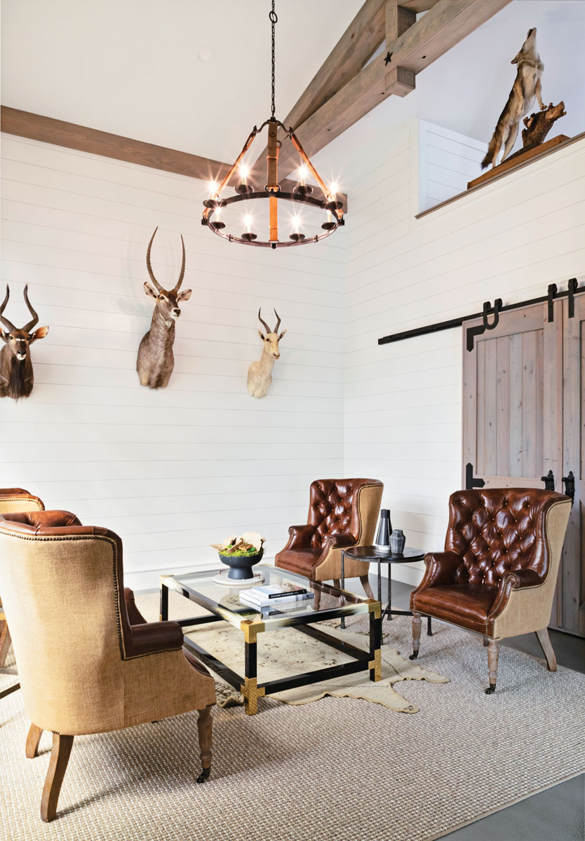 Timmerman created a gentleman's lounge tucked away from the hubbub, where Larry's friends can sip bourbon as they sit in high-backed leather chairs. Larry was granted additional leeway with a few more mounts in this space. A rustic barn door conceals his gun storage room.