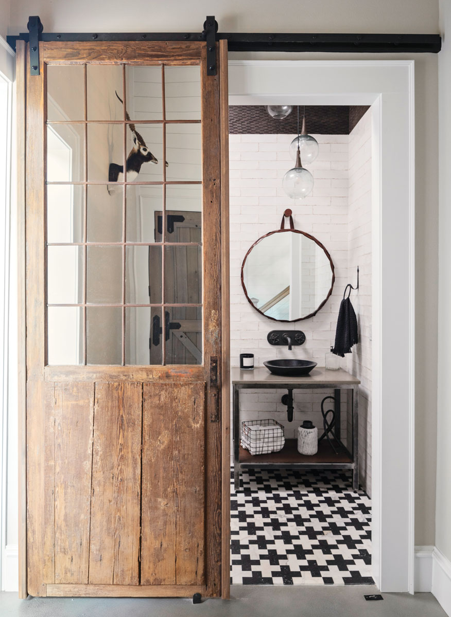 The powder room blends old and new to create a sparse but funky space, with graphic black and white floor tiles, an industrial vanity, subway tile, and a barn door that locks into the floor like a sliding stable door.