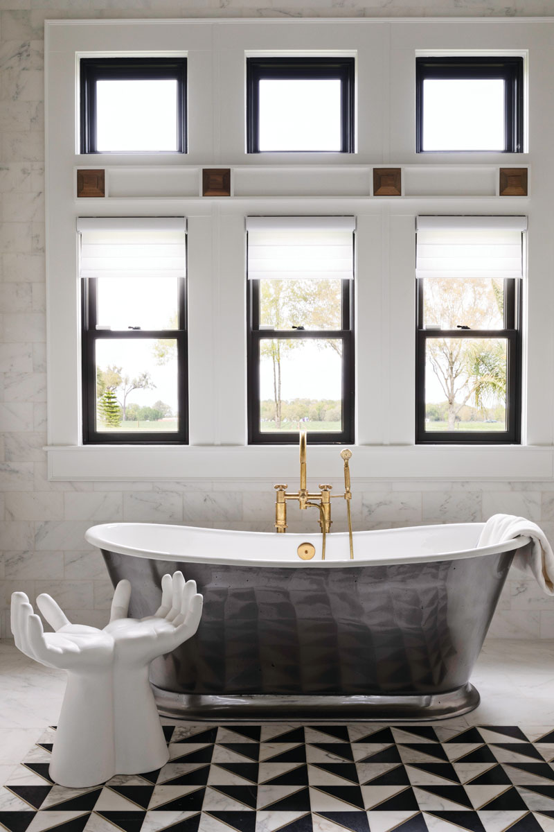 """The master bathroom gets more of the black and white treatment, mixing brass fixtures, polished nickel, and a hands-shaped chair """"just for a cheeky touch,"""" Timmerman says."""