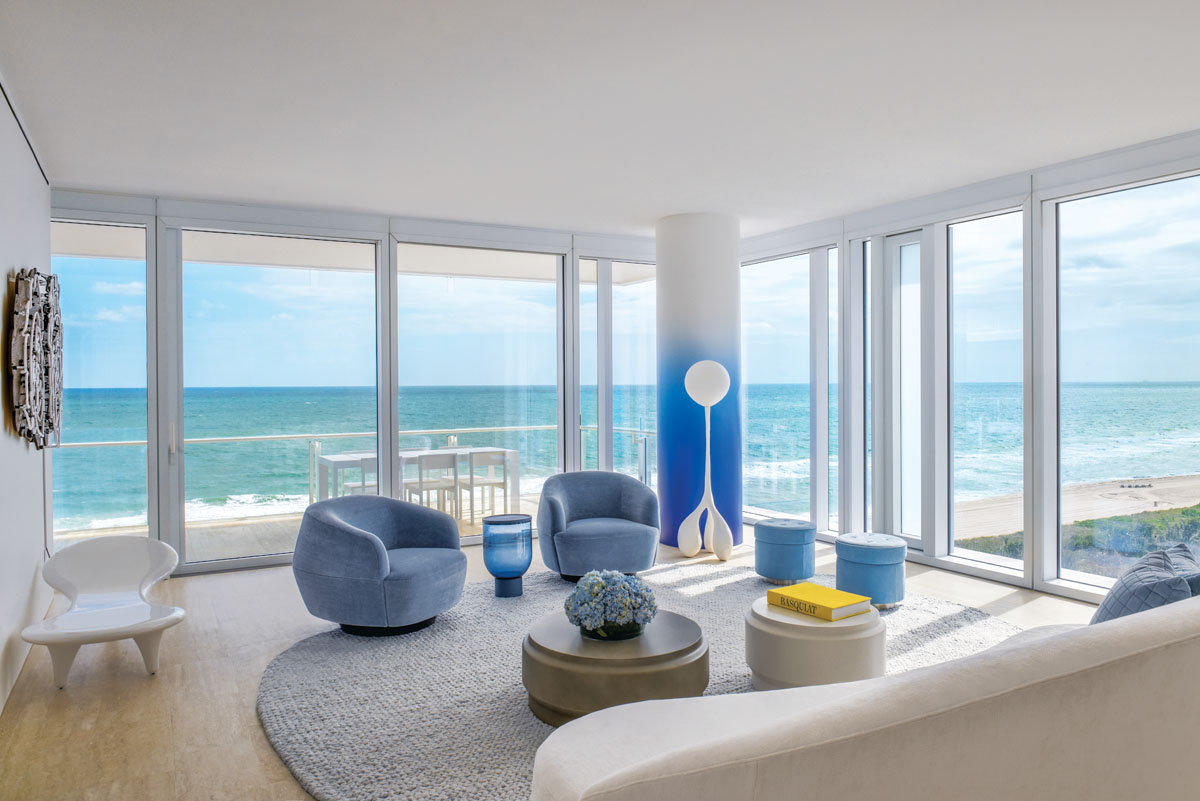 Waves washing up on the shore are visible from the expansive living room windows where Sumo Lounge Chairs and Lotus coffee tables from Holly Hunt echo the rounded lines of the Patrick Naggar sofa from Ralph Pucci and flank the transparent blue Mastea side table by Matteo Zorzenoni. Lighter shades of blue are carried through in the small India Mahdavi stools. The custom knit rug is a pale gray Atwood Cloud 5 by Kravet.