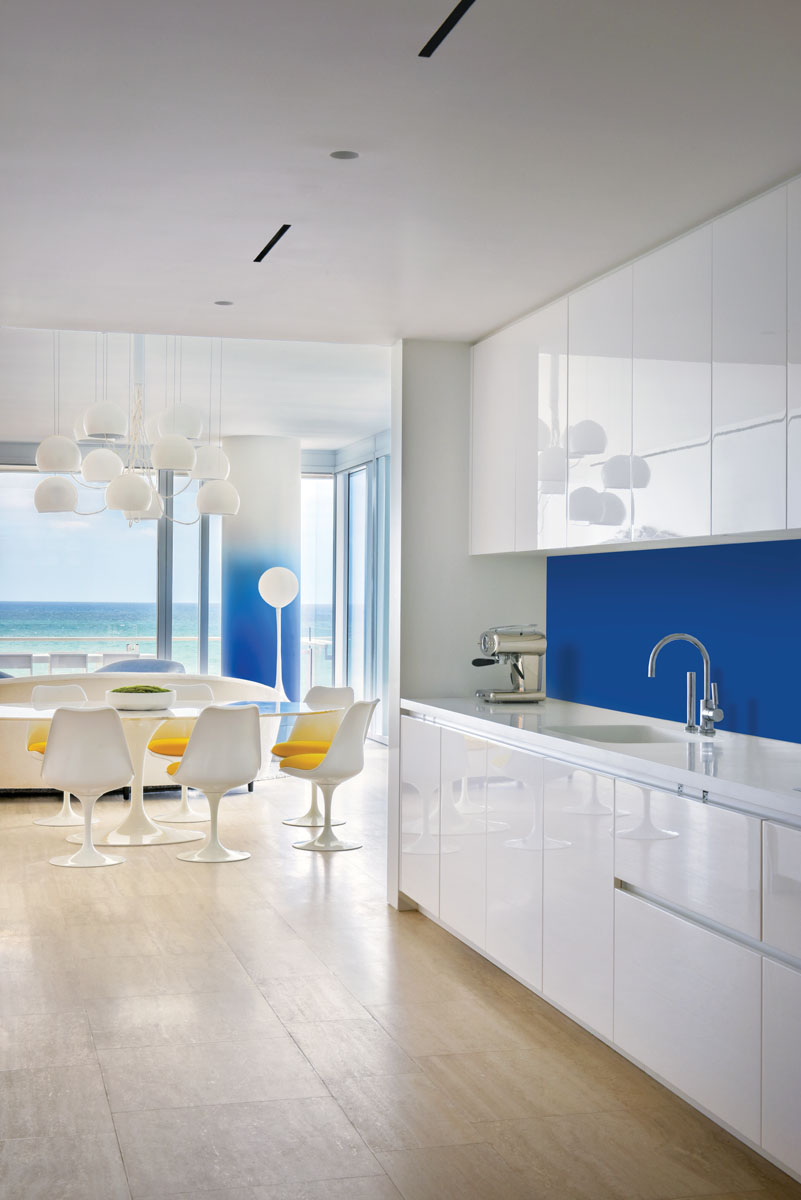 The gleaming white original Boffi kitchen was untouched by the designers except for adding the reverse-painted glass backsplash in the same Yves Klein blue used on the column.