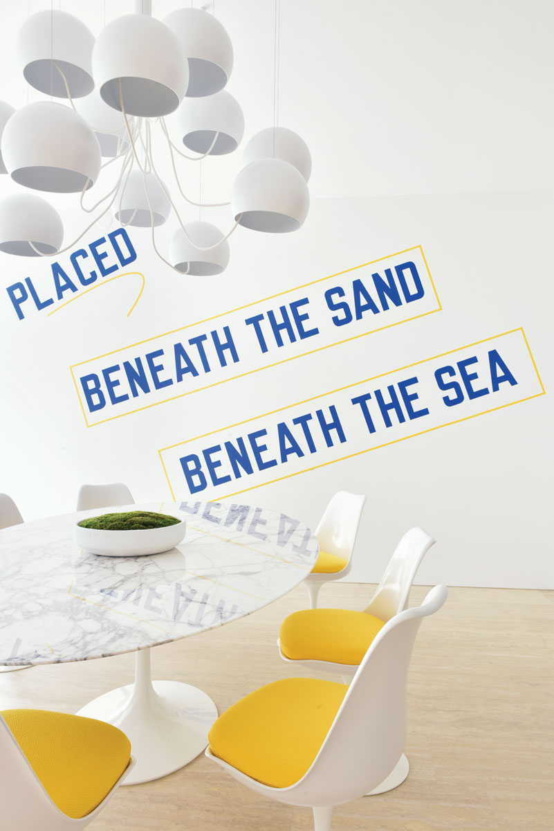A classic Saarinen pedestal table anchors the dining area below a massive white chandelier by Pierre Paulin. Pops of yellow were added on the Saarinen Tulip chair seats to reference the yellow family room sofa. Renowned conceptual artist Lawrence Weiner was flown in from New York to install his Placed Beneath the Sand, Beneath the Sea on site.