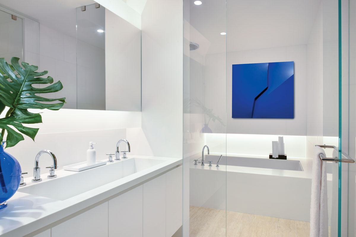 The pristine master bathroom was untouched except for adding a Delsy Rubio piece above the bathtub to carry the pop of blue onto the back wall.