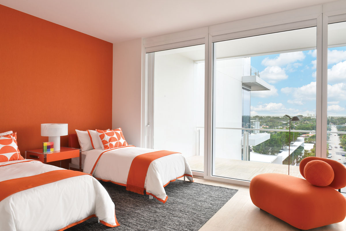 The daughter chose her favorite color for an accent wall which was covered in Insolence Temper Orange wallpaper. Although it took some convincing, after the kids got their own individual design presentations they agreed to have some pieces in common for design cohesiveness, including the nubby gray Vinegar Hill area rug, the lounge chair, and bedding by Serena & Lily.