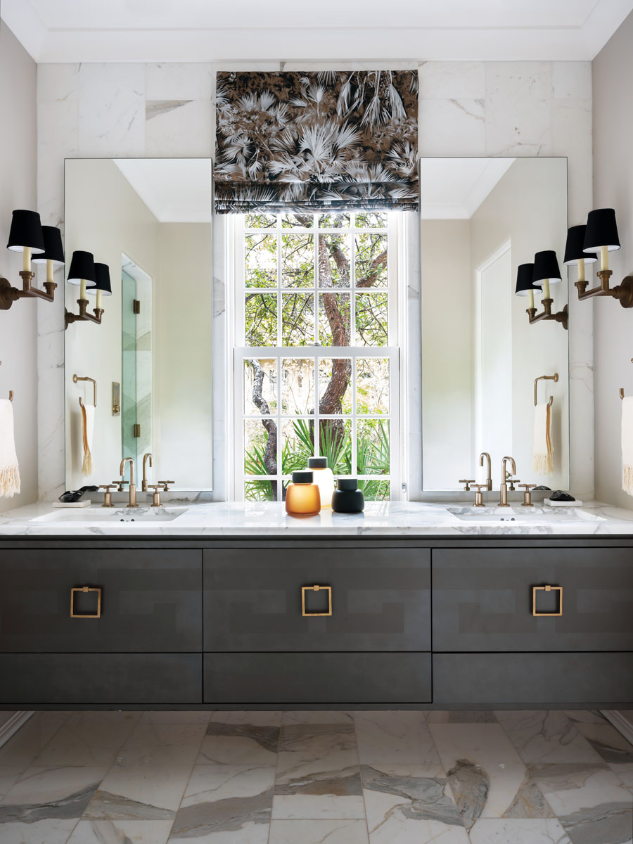 The light-filled master bathroom looks out over the home's lush front yard. Floating dual vanities in a heavy wood grain are anchored by Kohler fixtures.
