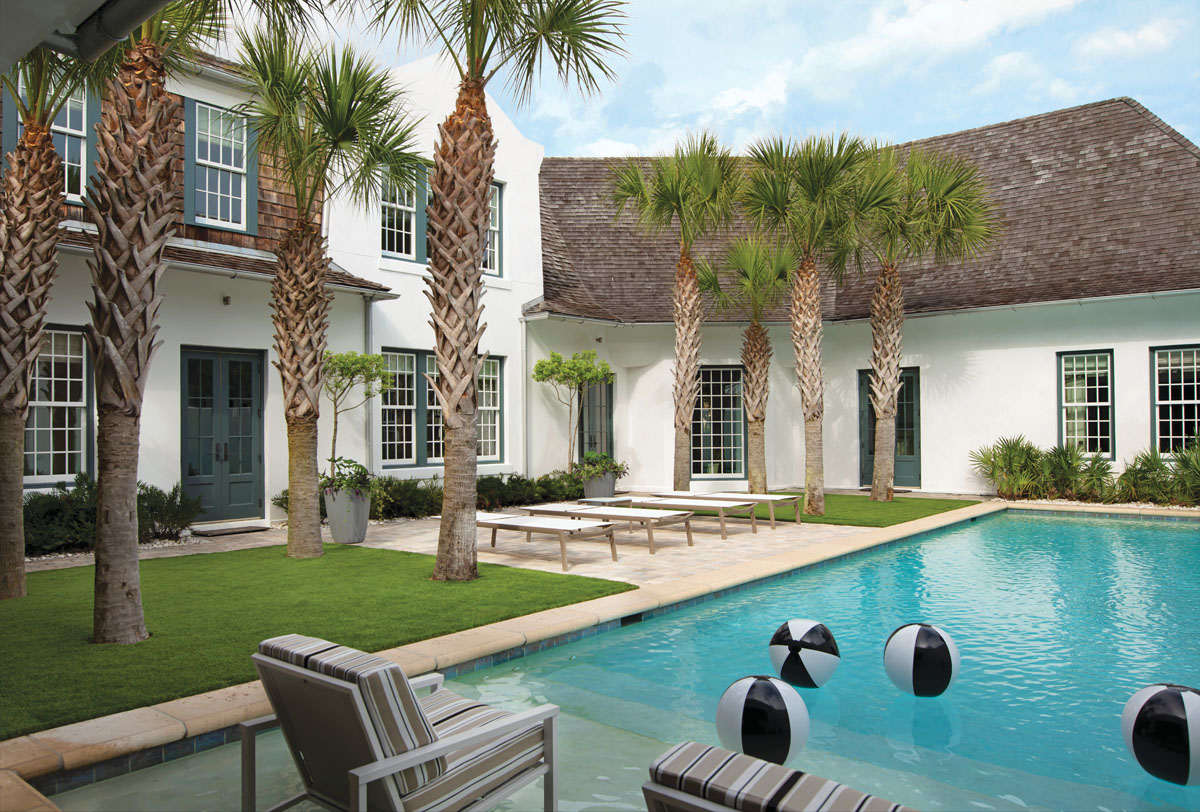 Nearly every one of the home's doors leads to the pool that runs the length of the corner lot. Savage kept the outdoor aesthetic clean and uncomplicated, including four white chaise lounge chairs and Perennials-upholstered sun chairs he placed on the top step of the the pool deck.