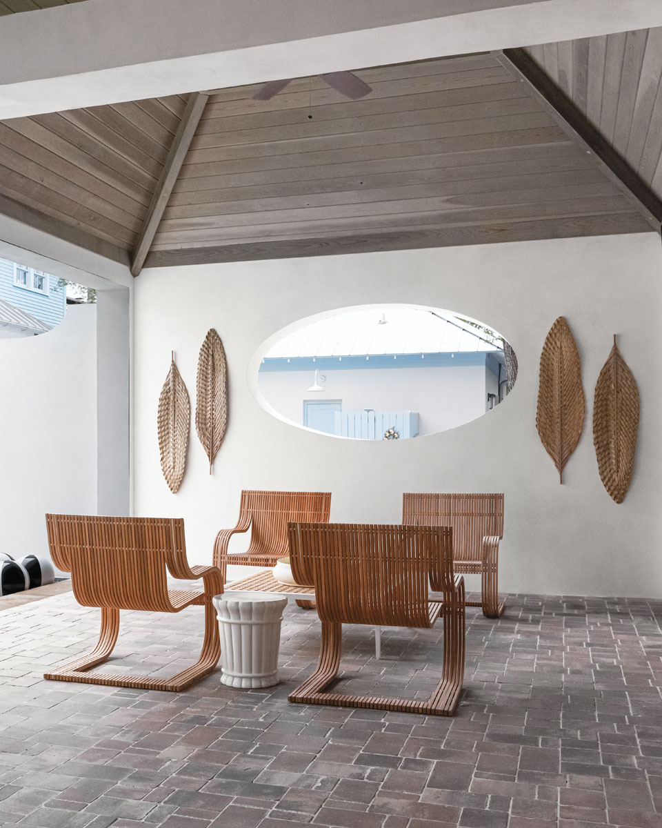 """""""Formal spaces are out. Intimate spaces are in to extend square footage and give the client options indoors or out,"""" Savage says. Seeing another opportunity for a poolside lounge area, he created underneath a peaked driftwood ceiling with a Janus et Cie coffee table and David Sutherland teak wood chairs. Dried woven palm fronds add texture to whitewashed walls."""