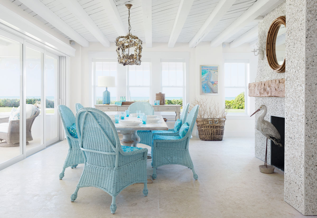 """On the first floor, the dining area showcases the cottage's original fireplace made of tabby— a mixture of concrete and crushed shells. The owners added the mantle, which interior designer Jett Thompson says gives the look of driftwood. The space can be connected to the patio, thanks to sliding glass doors that fold all the way back to create """"one great big, glorious room,"""" says Thompson."""