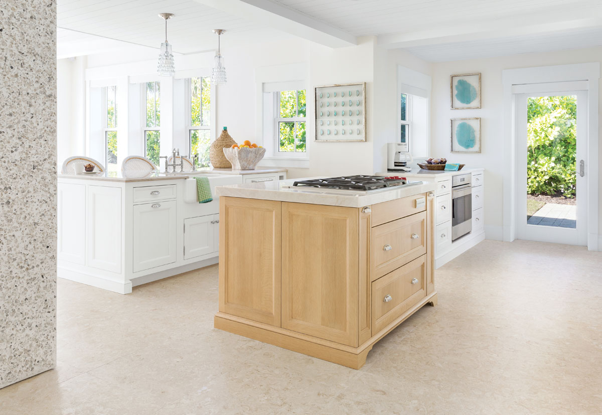"""Just off the dining area, the kitchen's oak island is a gathering spot for family. French barstools in woven plastic are simple to keep clean and light enough to move around with ease. Just behind the barstools is a small seating area with four club chairs and an ottoman. """"We did maximum seating in the house and nothing fussy,"""" says Thompson."""