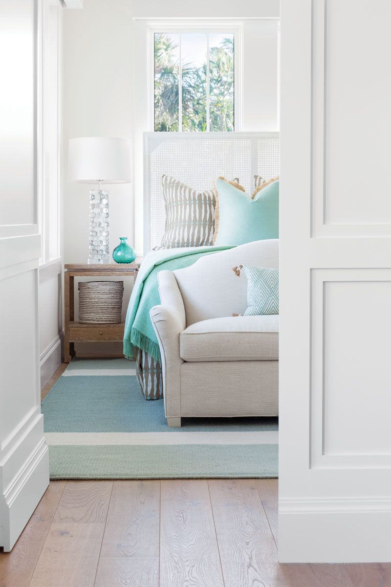 With windows everywhere, arranging the furniture in the bedrooms was a challenge. Thompson designed the headboards so they don't block light. When the guest bedroom doors are closed, they seamlessly blend into the paneling in the hallway.