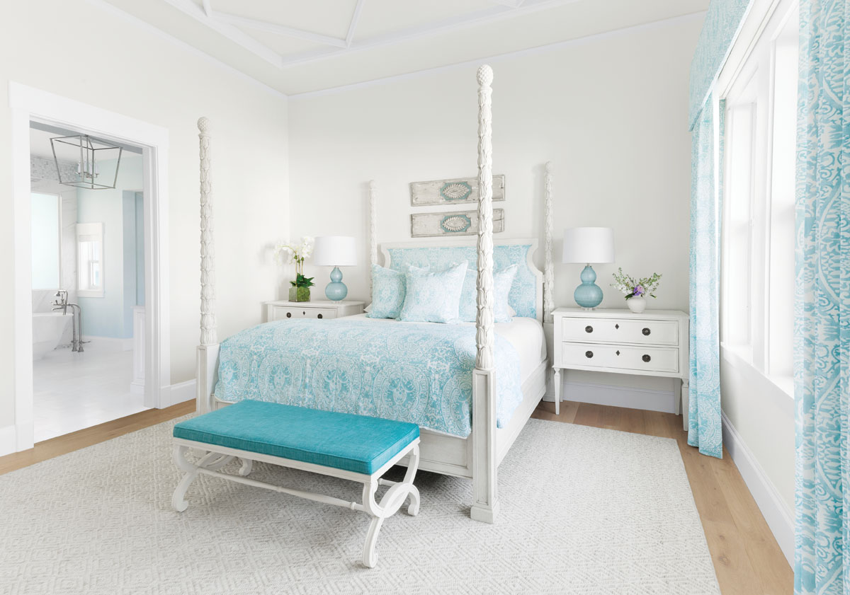 """Seventeenth-century Italian panels hang above the four-poster bed in the master bedroom. The bedding fabric is by Quadrille. """"We wanted to keep the color palette consistent throughout the house,"""" Thompson says. The view from the en suite bathroom looks out over the Gulf of Mexico."""